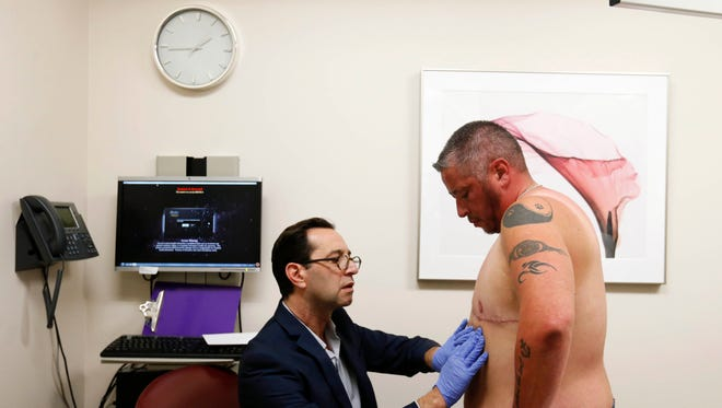 Dr. Clifford King examines Aiden DeLathower Monday, Nov. 7, 2016, during a follow-up appointment at Madison Cosmetic Surgery in Middleton, Wis. DeLathower had surgery to remove his breasts as part of his transition from female to male.