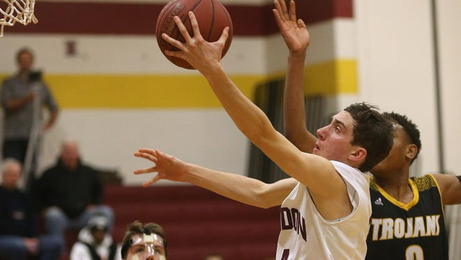 Mendon's Connor Krapf drives to the basket against Athena's Christian Jones.