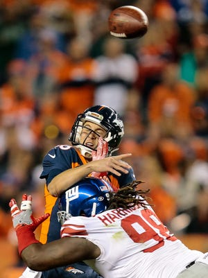 Denver Broncos quarterback Trevor Siemian (13) throws under pressure from New York Giants defensive tackle Damon Harrison Sr. (98) in the third quarter at Sports Authority Field at Mile High.