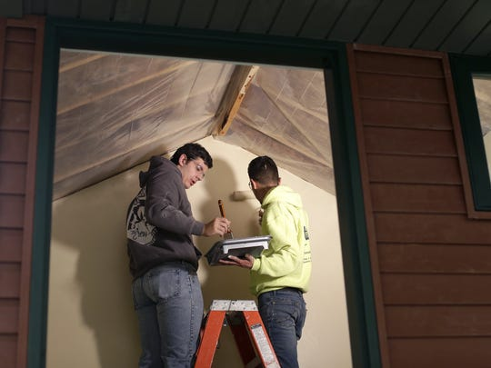 NWTC carpentry students Matthew Kaczmarek and Antonio Vargas paint a playhouse that will be sold at auction to benefit CASA of Brown County.