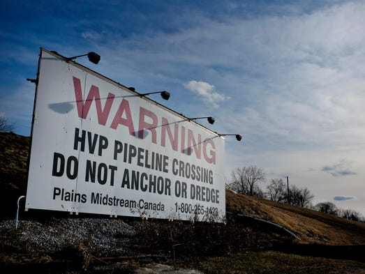 A sign warns boaters of a pipeline traveling under