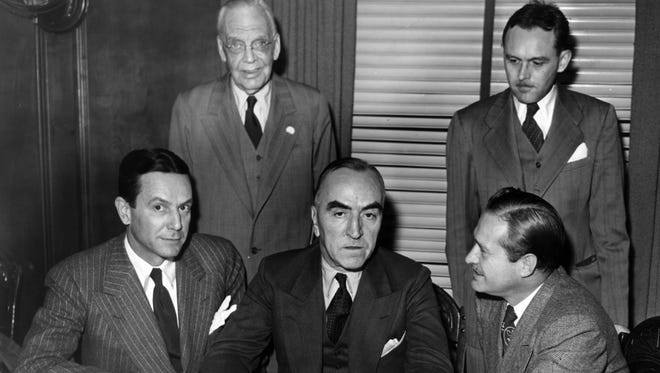 """Tony Hulman Jr of Terre Haute, Capt. Eddie Rickenbacker and three time Indianapolis 500 winner Wilbur Shaw sign the formal papers of transfer for the Indianapolis Motor Speedway Nov. 15, 1945.  Hulman purchase the track for$750,000.  Shaw became the speedway president. Watching from left is P.E. """"Pop"""" Myers and Joe Cloutier, secretary and who would later become the president of the speedway in 1977."""