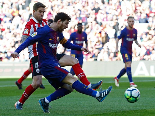 FC Barcelona's Lionel Messi, foregound, kicks the ball during the Spanish La Liga soccer match between FC Barcelona and Athletic Bilbao at the Camp Nou stadium in Barcelona, Spain, Sunday, March 18, 2018. (AP Photo/Manu Fernandez)