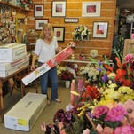 Birgitt Hunt, owner of Country Charm Florist & Gifts, at 3234 West New Haven Avenue in West Melbourne, processing boxes of flowers from wholesalers that arrived to make Mother's Day arrangements later in the week.