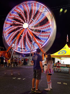 The Ferris wheel creates brilliant colors as it spins on the midway at the 2016 Tennessee State Fair on Sept. 17, 2016, in Nashville.