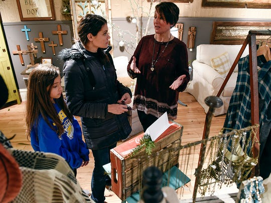 Mary Franke, Marishka's Shoppe, right, helps Amanda Anderson, St. Augusta, and her daughter Isabelle, 10, find a gift Tuesday, Nov. 22, amongst the women's clothing, jewelry and home decor items in the store.