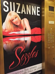 Signs promoting the show Suzanne Sizzles, like this