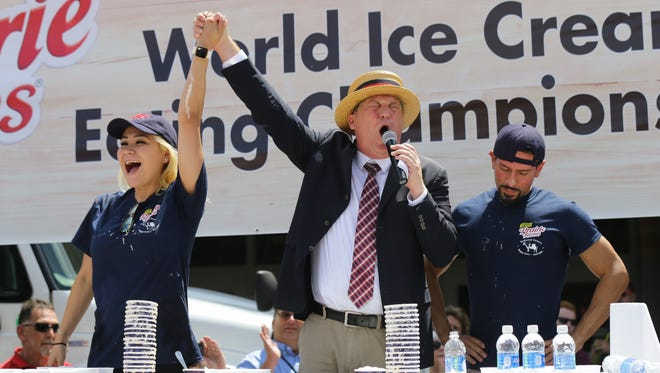 Major League Eating Emcee Sam Barclay, right, congratulates Miki Sudo, left, on setting a world record for eating the most pints of ice cream while second place eater Juan Rodriguez, right, recovers from the first-ever World Ice Cream Eating Championship at the Indiana State Fair in Indianapolis on Sunday, August 13, 2017.