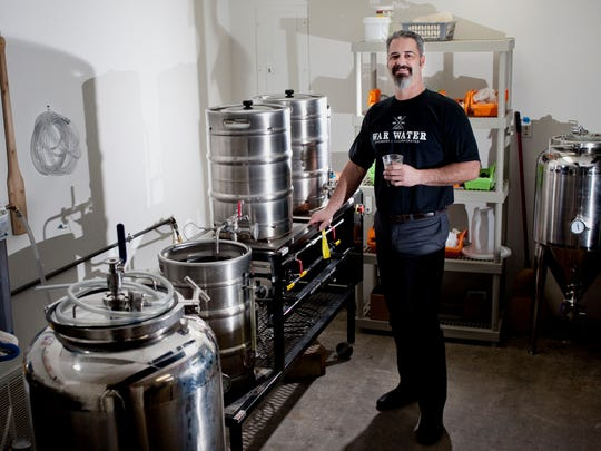 Kris Paul poses with brewing equipment Thursday, March 26, 2015 at War Water Brewery in St. Clair. The temporary location has been set up at 201 N. Riverside Ave., Suite C-12, until a location for a larger commercial brewing operation is established.