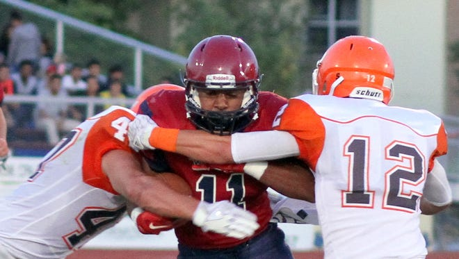 Wildcat back Nicholas Soledad (11) is wrapped up by a pair of Artesia defenders during Friday's 49-6 home loss to the Bulldogs.
