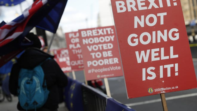 Anti Brexit and pro European Union protesters carry flags and placards as they demonstrate outside the Palace of Westminster in London, Monday, March 11, 2019. British Prime Minister Theresa May still hopes to secure changes from the EU that can win U.K. lawmakers' backing for her Brexit deal, despite a lack of progress in last-minute talks.
