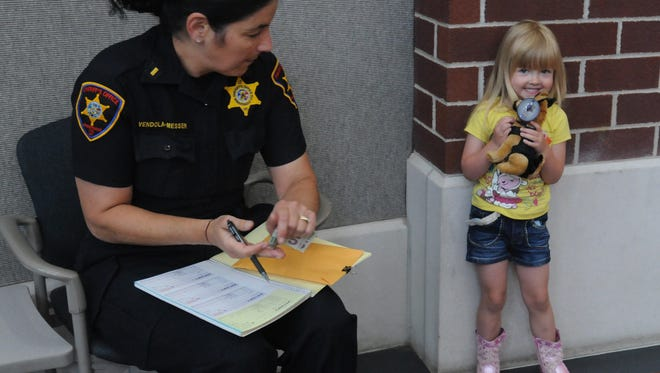 Lt. Lara Vendola-Messer of the Winnebago County Sheriffs Office receives a donation from Emma Hughes, 3, for one of the stuffed dogs as part of a fund raising program for the K-9 units.  The money raised will go toward upkeep and maintenance of the dogs and outfitting the dogs with special collars and equipment.