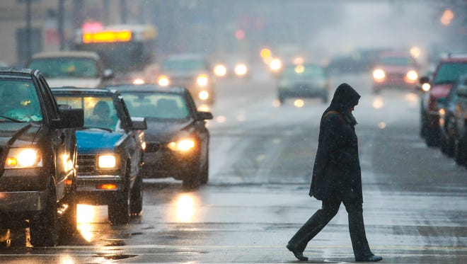 A pedestrian makes their way across the street as snow moves in Wednesday evening in downtown Louisville. March 4, 2015