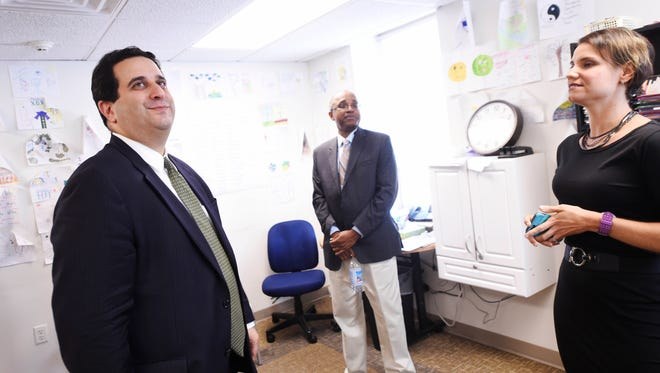 Department of Human Services Secretary Ted Dallas, left, tours a group room where therapy sessions are led, with Trish Young, vice president of outpatient services at Pennsylvania Counseling Services.