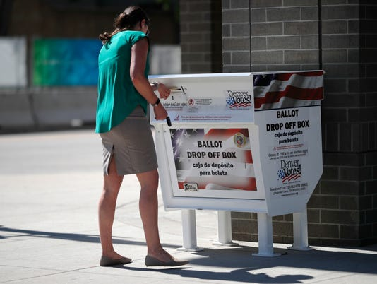 Voters drops off ballot in collection box, r m