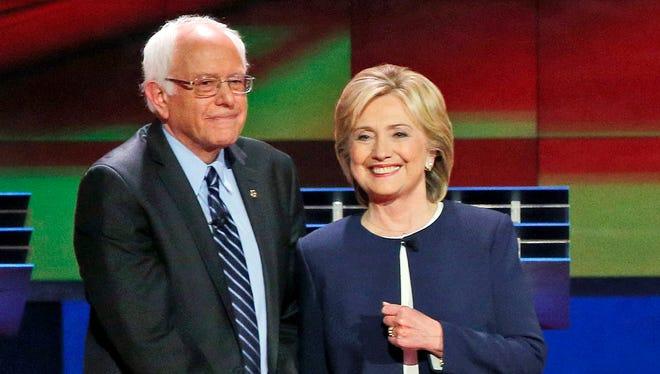 Democratic presidential candidates Sen. Bernie Sanders, I-Vt., left, and Hillary Clinton talk before the CNN Democratic presidential debate in Las Vegas on Oct. 13, 2015.