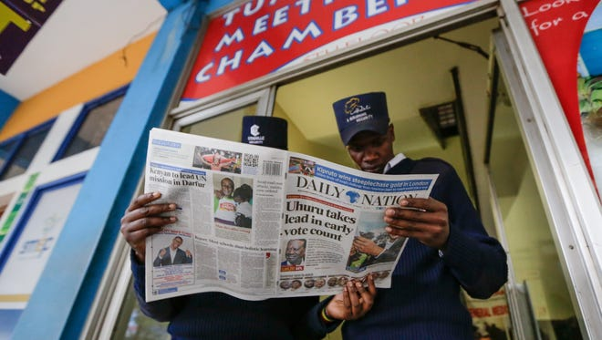Kenyan security guards read one of the local newspapers with headlines on the early lead by President Uhuru Kenyatta in the streets of Nairobi, Kenya, Aug. 9, 2017.