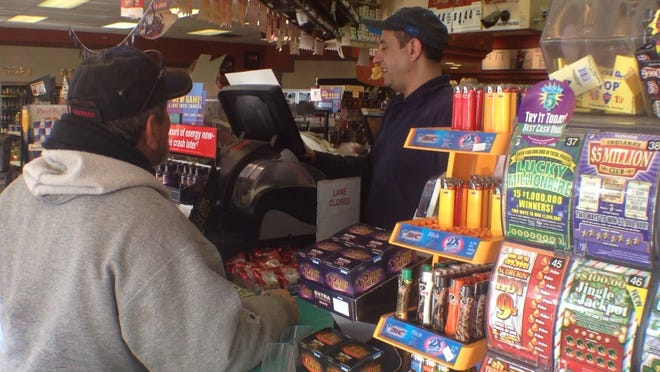 A gas station owner sells lottery tickes to a customer. (Michelle Pemberton/The Star)