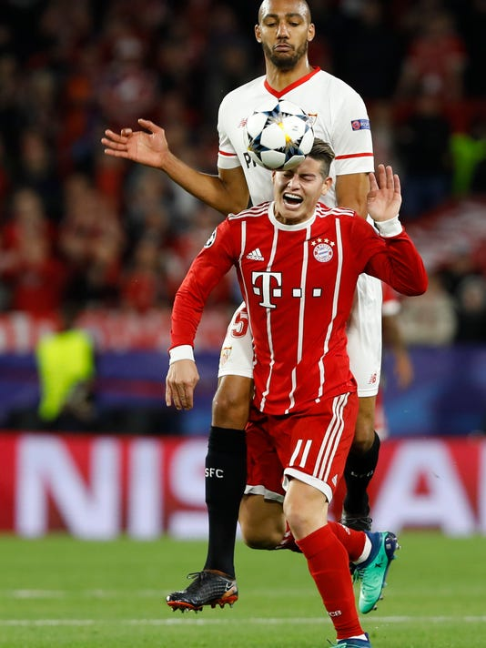 Sevilla's Steven N'Zonzi, top, and Bayern's James challenge for the ball during the Champions League quarter final first leg soccer match between Sevilla FC and FC Bayern Munich at the Sanchez Pizjuan stadium in Seville, Spain, Tuesday, April 3, 2018. (AP Photo/Miguel Morenatti)