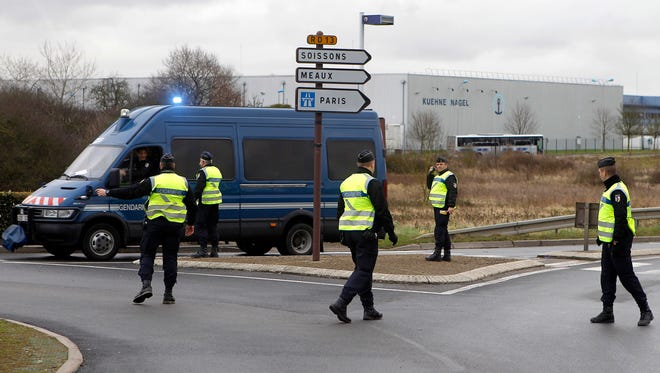 Police oficers direct the traffic at an intersection in Dammartin-en-Goele, northeast of Paris, on Jan. 10, 2015.