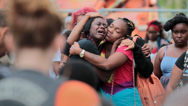 Friends, family members and neighborhood residents grieve together in the parking lot of the Girls & Boys Club of Rochester during a vigil there Thursday night, Aug. 20, 2015.