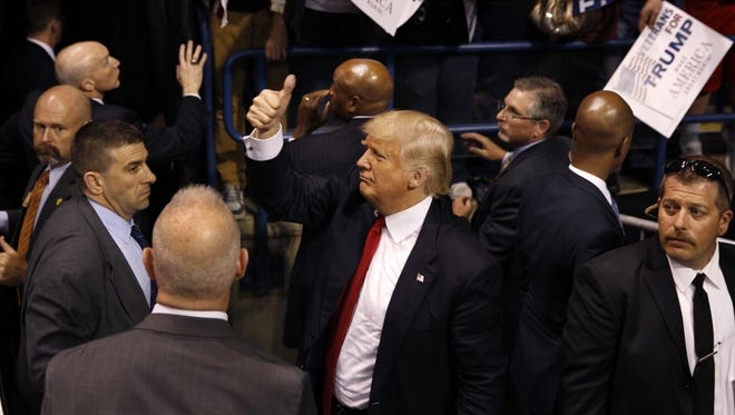 Security stands nearby as Republican presidential candidate, Donald Trump, center, gives a thumbs up to supporters after speaking at a campaign rally Monday, April 25, 2016, in Wilkes-Barre, Pa.
