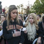 Florida State University student Colleen Rick, left, passes the flame to her fellow students during the Gathering of Unity candlelight vigil on campus after the shooting of three students earlier in the day in Tallahassee.