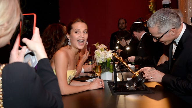 Alicia Vikander smiles wide while watching her Oscar get engraved with her name.