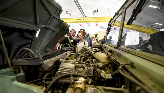 Students from Mansfield Senior High School get a close look at the construction of a military Humvee on Wednesday during  the Technician for a Day program with local employers on the Ohio National Guard base.