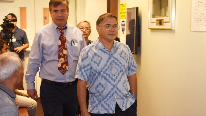 Guam Housing and Urban Renewal Authority Executive Director Michael Duenas, front, exits the coutroom accompanied by his attorney John Terlaje after his arraignment at the Superior Court of Guam on Aug. 23, 2017. Duenas and former GHURA board members pleaded not guilty to misdemeanor charges related to alleged secret meetings.
