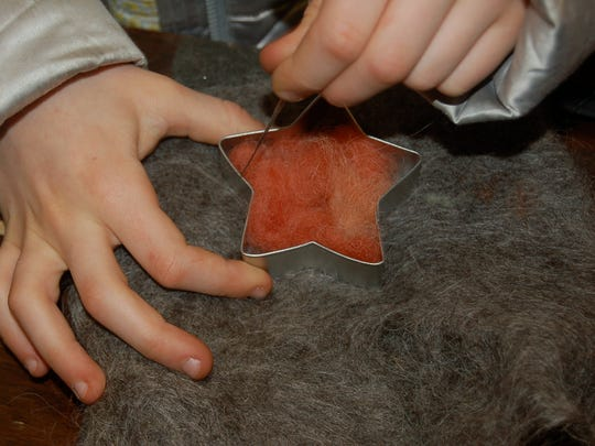 A participant makes a hand-made felted ornament at Common Ground Farm's Holiday Felting Project in 2013
