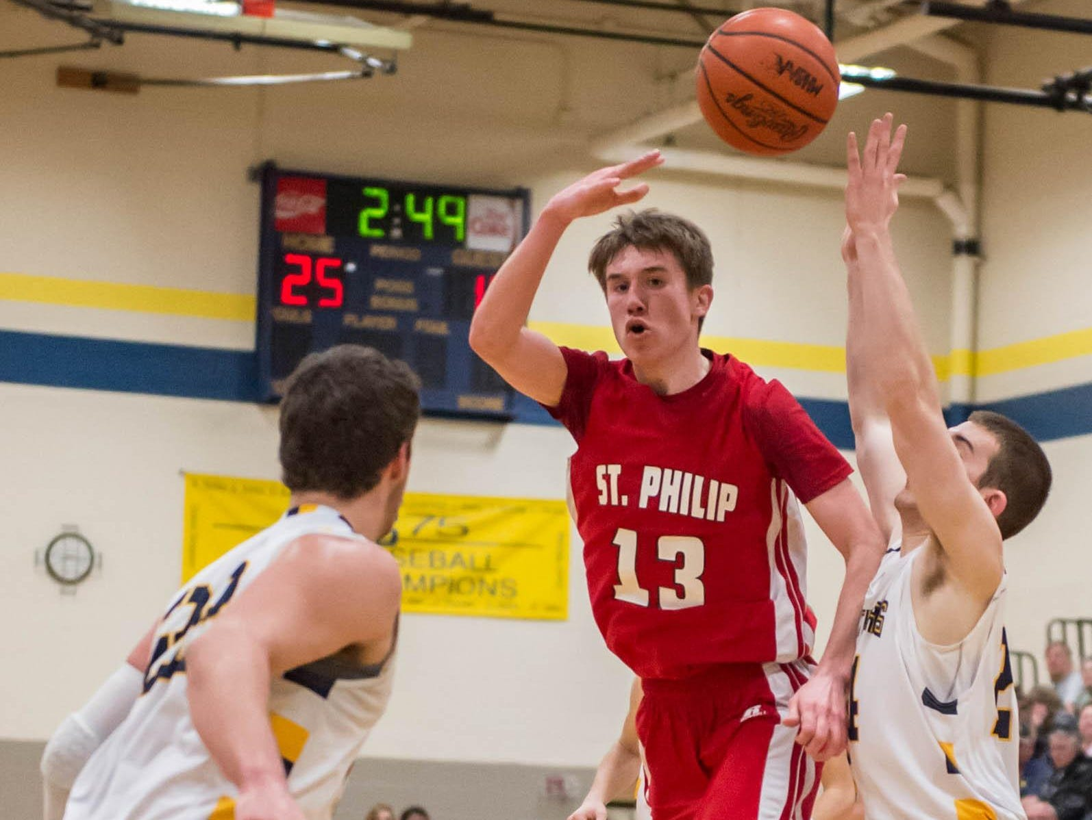 St. Philip's Drew Lantinga (13) throws a no-look pass over a Climax-Scotts defender in action earlier this season.