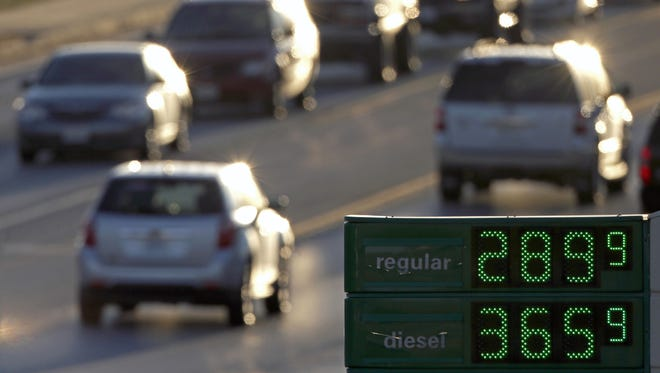 In this Tuesday, Nov. 26, 2013, file photo, motorists drive past a gas station selling regular unleaded gasoline for less than $3.00 a gallon, in Independence, Mo. Higher gasoline prices are on the way for 2014, but the spring surge may be tamer than in recent years.