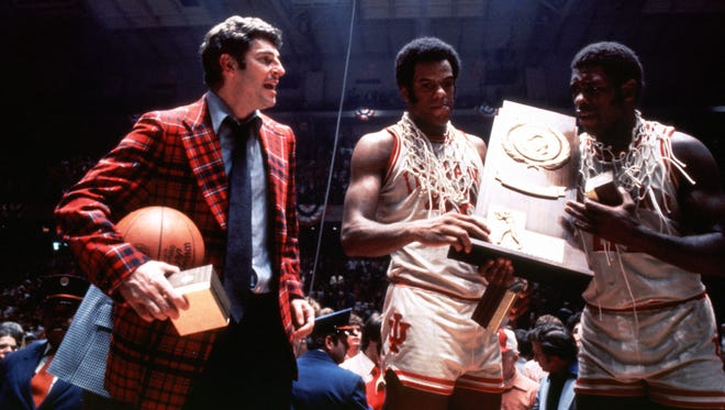 Indiana University coach Bob Knight with the winning basketball and Scott May (42) and Quinn Buckner (21) celebrate their NCAA championship after defeating Michigan 86-68 in Philadelphia.