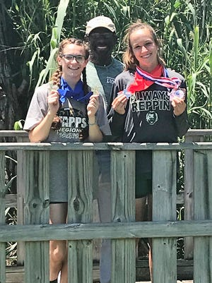 Cornerstone's Jessica Simon, left, and Hannah Slate, right, show off their medals won at the TAPPS  Class 1A State Track and Field Championships Saturday, May 5, 2018, in Waco. With them is Cornerstone track coach Gary Gabriel.