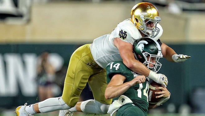 Michigan State quarterback Brian Lewerke is tackled by Notre Dame's Nick Coleman during the first half at Spartan Stadium on Sept. 23, 2017.
