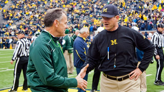 Michigan State coach Mark Dantonio shakes hands with Michigan coach Jim Harbaugh on the Michigan Stadium field before an NCAA college football game in Ann Arbor, Mich., Saturday, Oct. 17, 2015. (AP Photo/Tony Ding)
