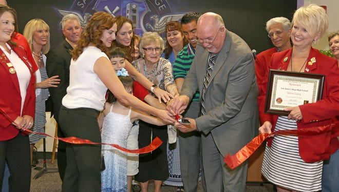 At center, Don Lorett, principal at San Juan College High School, cuts the ribbon during a ribbon-cutting ceremony for the new school on Aug. 19. The school is the first early college high school in New Mexico that represents a partnership between a community college and four school districts. Eighty students from the Farmington, Aztec, Bloomfield and Central Consolidated school districts are enrolled in the school. Graduates will earn both a high school diploma and an associate degree. The new school is located next to the Learning Commons Plaza at San Juan College in Farmington.