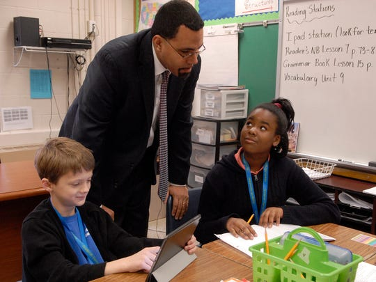 U.S. Secretary of Education John King Jr., center, talks with fourth graders, Grayson Beverly, 9, left, and Kahlia Giles, 9, right, at Goldsmith Elementary School.  King was there to promote diversity and speak in a roundtable discussion with other community leaders.   Dec. 13, 2016