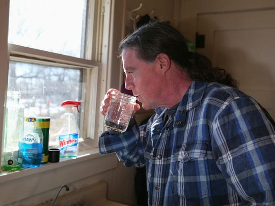 Joe Monahan takes a drink of water from the kitchen