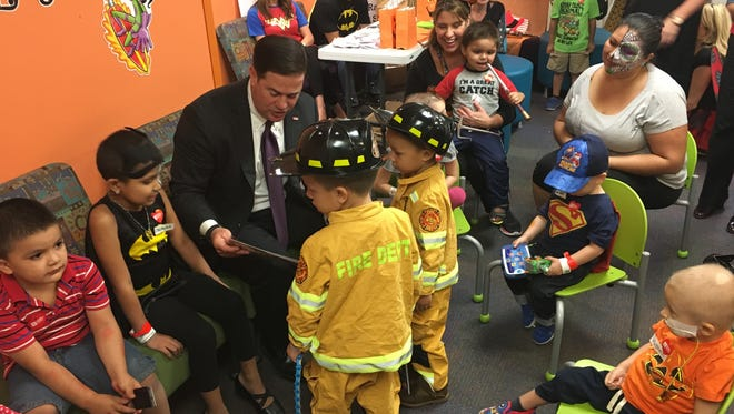 """Gov. Doug Ducey meets with patients at Phoenix Children's Hospital for """"reverse trick or treating."""""""