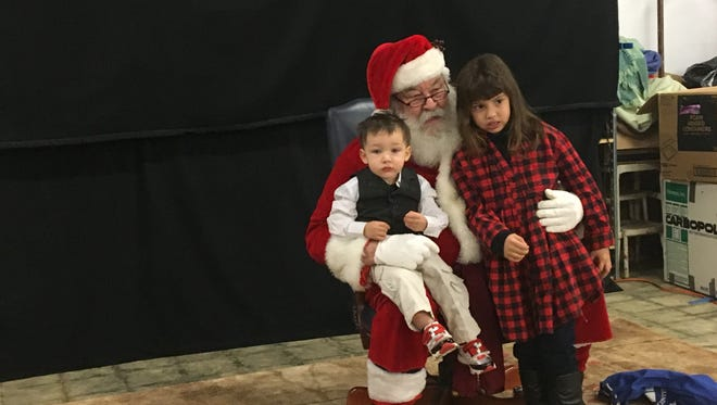 Bentley and Isabelle Kulikowski pose for portraits with Santa on Saturday at Regional Inter-Faith Association.