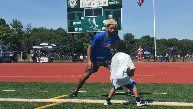 New York Giants wide receiver Odell Beckham Jr. interacts with a camper during a drill at his annual youth football camp.