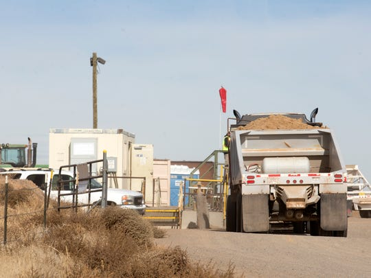 Trucks operate at the Evirotech land farm on Monday south of Bloomfield.