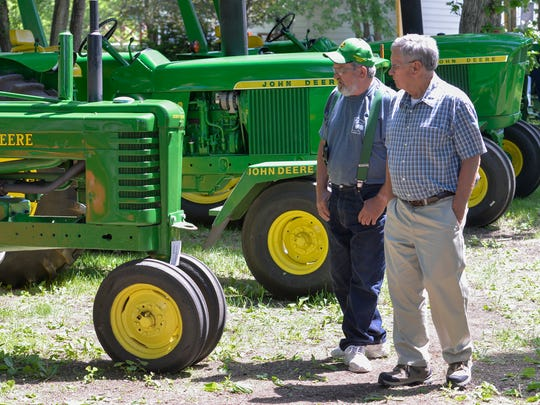 Ben Kuklock, left, of the Greater Minnesota Two-Cylinder Club, talks to Ron Paulson of Sauk Rapids as they survey the tractors on display Sunday at the Artisan Showcase & Antique Tractor Show at the Riverwood Mall.