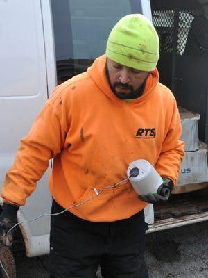 """In this file photo, RTS Water Solutions installation/repair technician Mike Sedillos prepares to install a 'smart' water meter. Installation began in July 2016 and was completed around spring 2017. After a year in place, the city said they are """"very satisfied"""" with the system."""