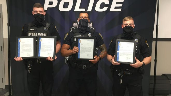 Patrolmen Nathaniel Koch (left), Christopher Hartzler and Michael Egbert were recognized for their actions during a May incident and received the Lifesaving Award.