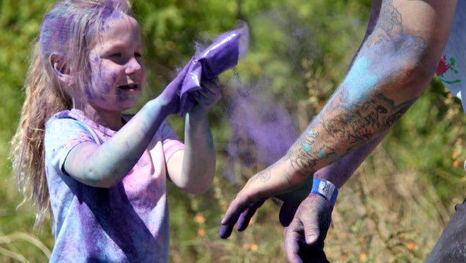Ruby Pardue chases her dad, Ronnie, with the last of her purple paint dust after the 4-H Powder to the People 5K fun run on Saturday at Voiers' Park. The run was a fundraiser to benefit Luna County 4-H.