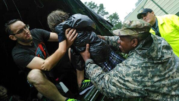 1st. Sgt. Bruce Jackson of Mansura, Louisiana, C Co, 769th Brigade Engineer Battalion, 256th Infantry Brigade Combat Team, lifts four-year old Zoe Trappey from Highland Ridge in Youngsville, Louisiana, to her parents in a high-water vehicle in Lafayette, Aug. 13, 2016. The Louisiana National Guard has mobilized more than 1,000 personnel in support of heavy flash flooding operations.
