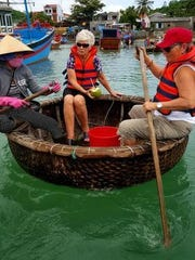 Attempting to navigate in a round basket boat used by Vietnamese fishermen to travel between the shore and their fishing boats.